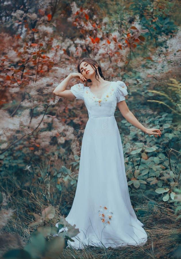 Загадочная дама самостоятельно в красочном лесе феи, танцующ с ее глазами закрыла, поднимающ ее руку к ее щеке, темн-с волосами стоковое фото