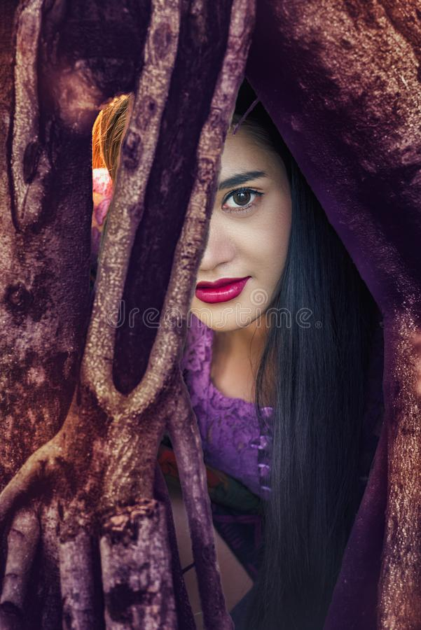 Загадочная женщина, красивая женщина с длинными темными волосами и красные губы отдыхая в корнях дерева и смотря вас стоковые фотографии rf