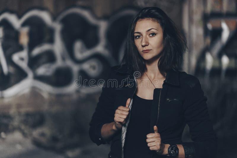 Загадочная красивая женщина в черном bodysuit и кожаная куртка с татуировкой хны на ее ногах сидя на старых каменных шагах с стоковые изображения