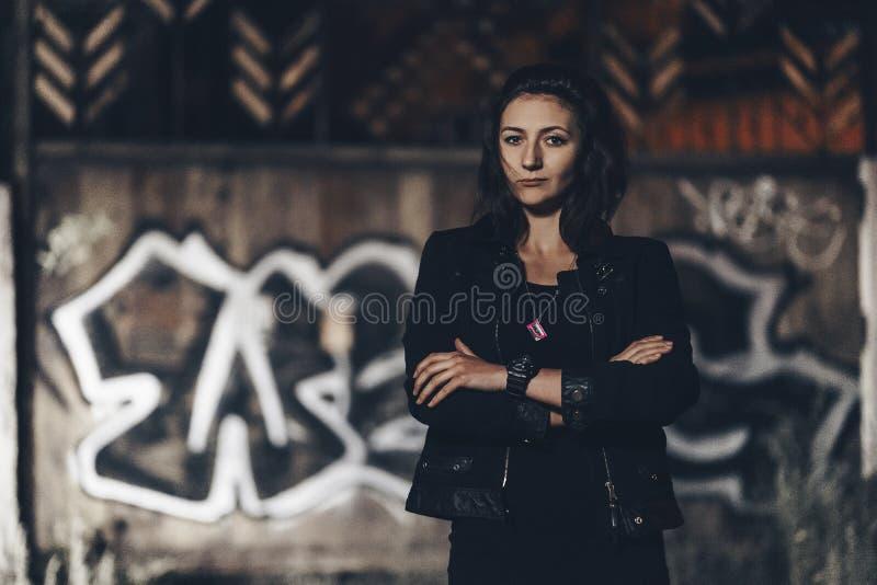 Загадочная красивая женщина в черном bodysuit и кожаная куртка с татуировкой хны на ее ногах сидя на старых каменных шагах с стоковое изображение rf