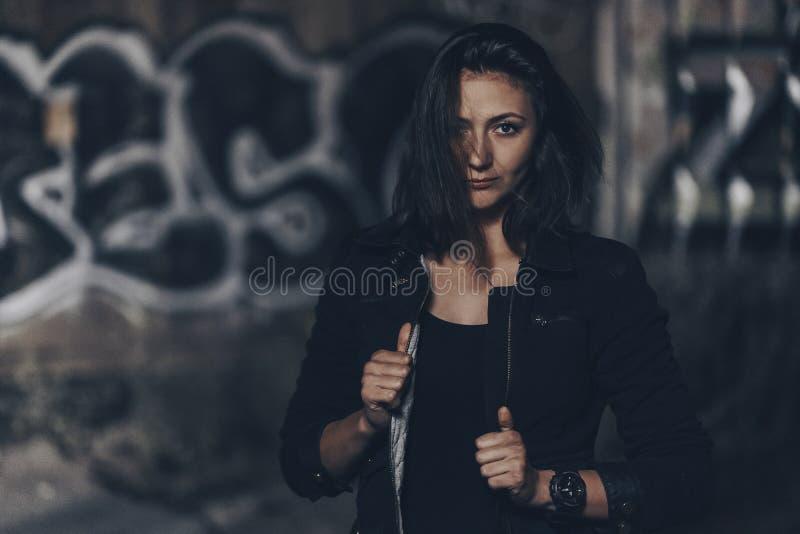 Загадочная красивая женщина в черном bodysuit и кожаная куртка с татуировкой хны на ее ногах сидя на старых каменных шагах с стоковое фото