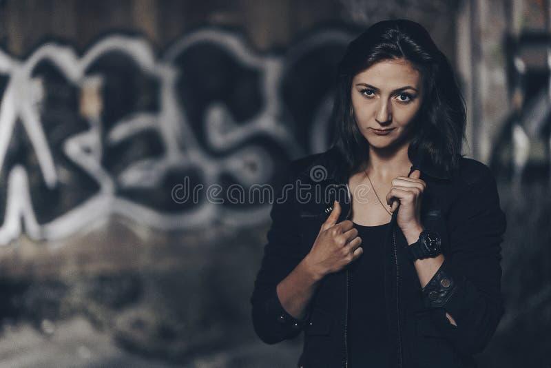Загадочная красивая женщина в черном bodysuit и кожаная куртка с татуировкой хны на ее ногах сидя на старых каменных шагах с стоковое изображение