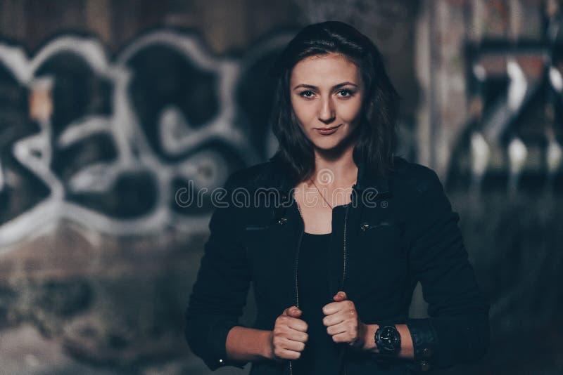 Загадочная красивая женщина в черном bodysuit и кожаная куртка с татуировкой хны на ее ногах сидя на старых каменных шагах с стоковые фото
