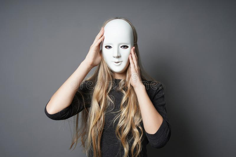 Загадочная молодая женщина регулируя ее маску стоковое фото rf