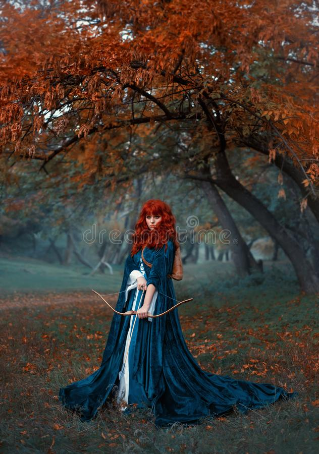 Загадочная рыжеволосая девушка воина стойки защищают над ее землей, храброй принцессой держит лук и стрелы, подготавливая для стоковая фотография