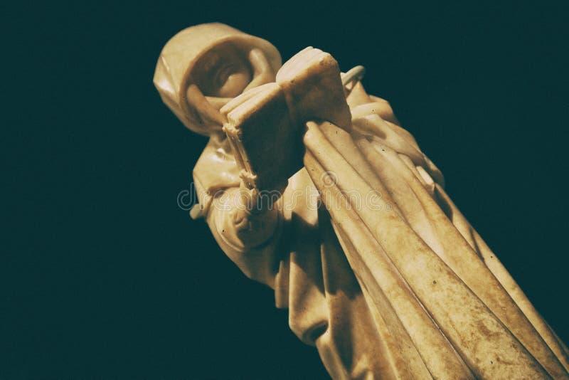 Загадочная статуя монаха friar читая книгу стоковые изображения rf
