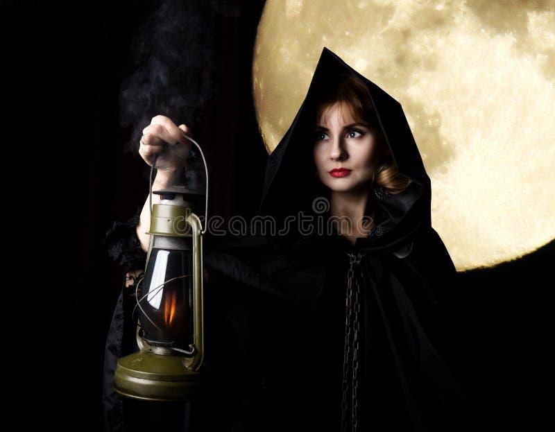 Загадочная молодая женщина держа веревочку и старый электрофонарь на темной предпосылке луны стоковая фотография