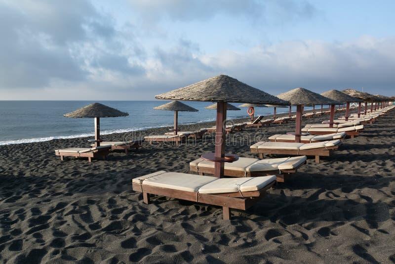 Загорая кровати и зонтики на Perissa приставают к берегу, Santorini, Греция стоковая фотография