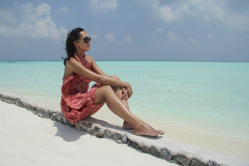 Загоренная девушка в красном pareo в мальдивском пляже стоковое изображение rf