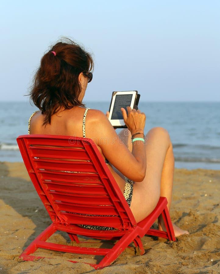 Загоренная женщина читает ebook на пляже стоковая фотография rf