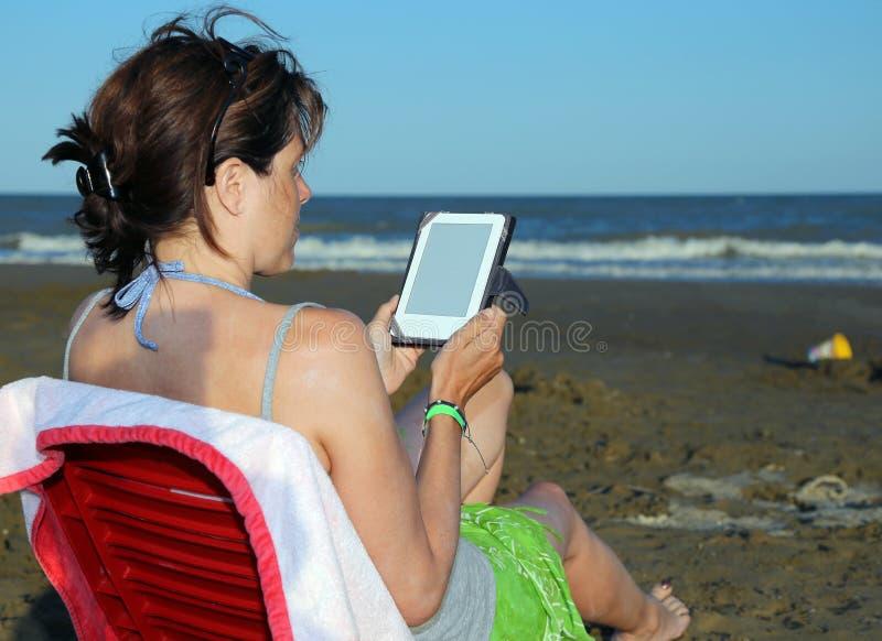 Загоренная женщина читает ebook на seashore стоковая фотография rf