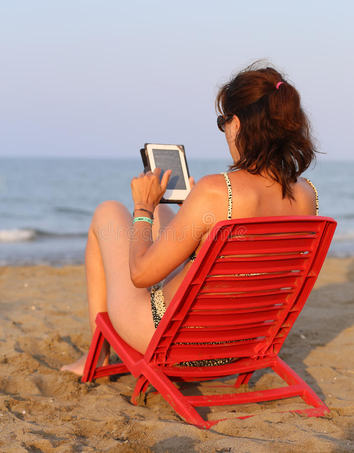 Загоренная женщина читает ebook на seashore i стоковое изображение