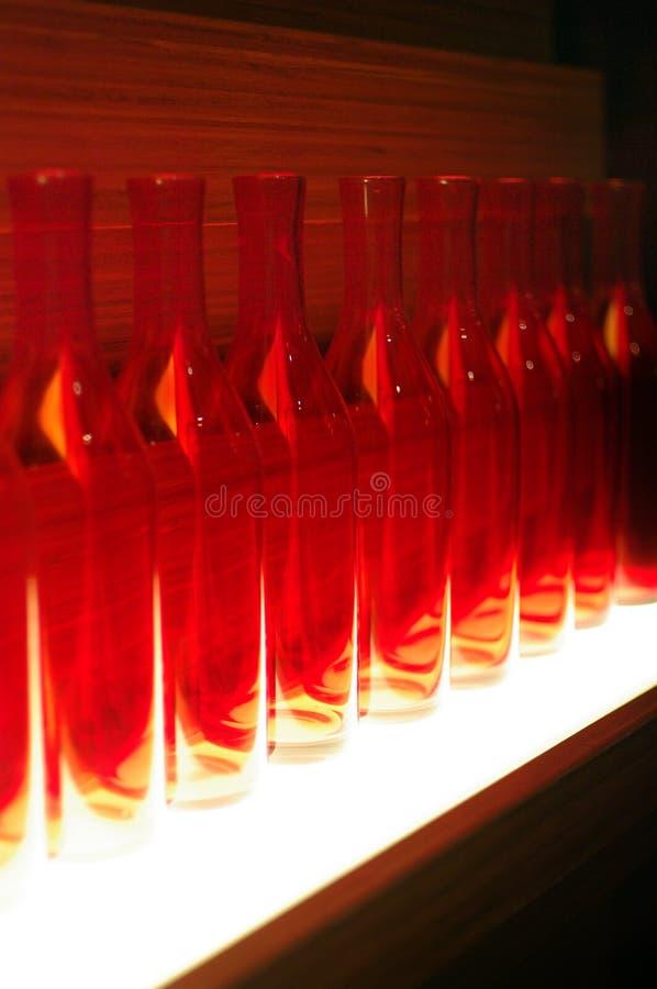 Загоренная красным светом предпосылка стеклянных бутылок абстрактная стоковое фото rf