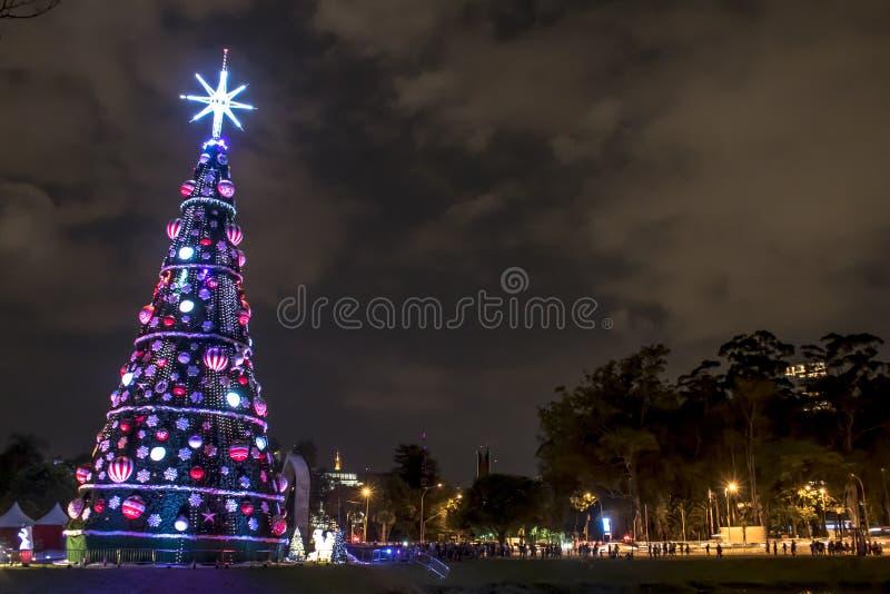 Загоренная традиционная рождественская елка в Ibirapuera, вечером, оно привлекательности в южной зоне города Сан-Паулу стоковое фото rf