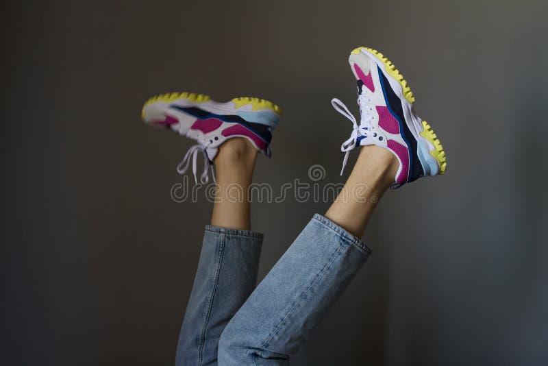 Загоренные красивые ноги тонкой молодой женщины в ультрамодных тощих голубых джинсах и новых красочных тапках спорта на серой пре стоковые фотографии rf