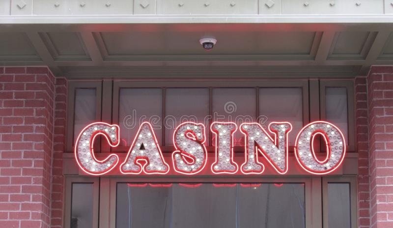 Загоренный знак казино вися вне входа к казино стоковая фотография