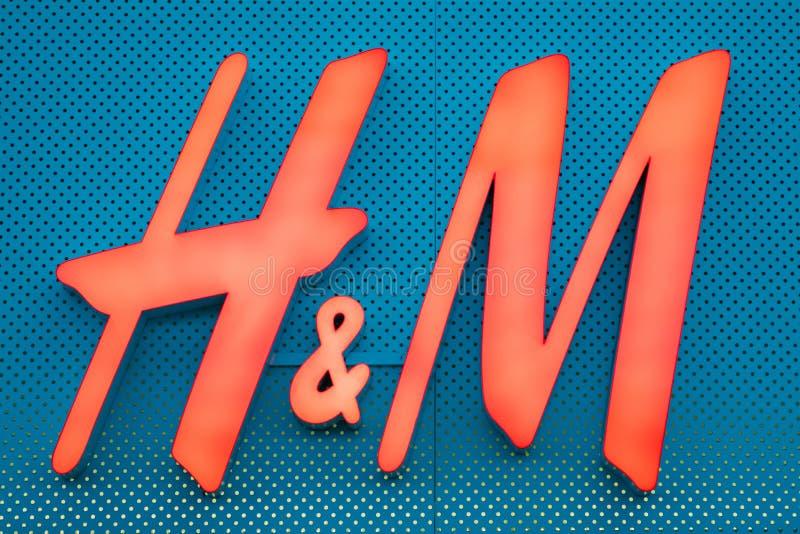 Загоренный красный логотип h m бренда Hennes Mauritz на голубой стене стоковые фотографии rf