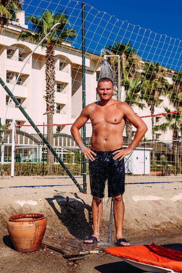 Загоренный человек в шортах стоя под холодным ливнем на пляже летом стоковые фото
