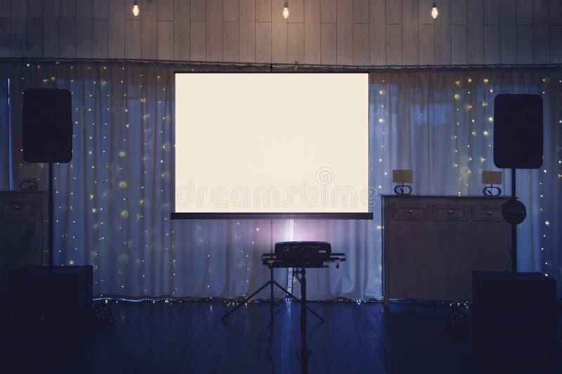 Загоренный этап залы банкетки с большим белым экраном и акустическими системами Оборудование для видео- и тональнозвуковой проекц стоковое фото rf