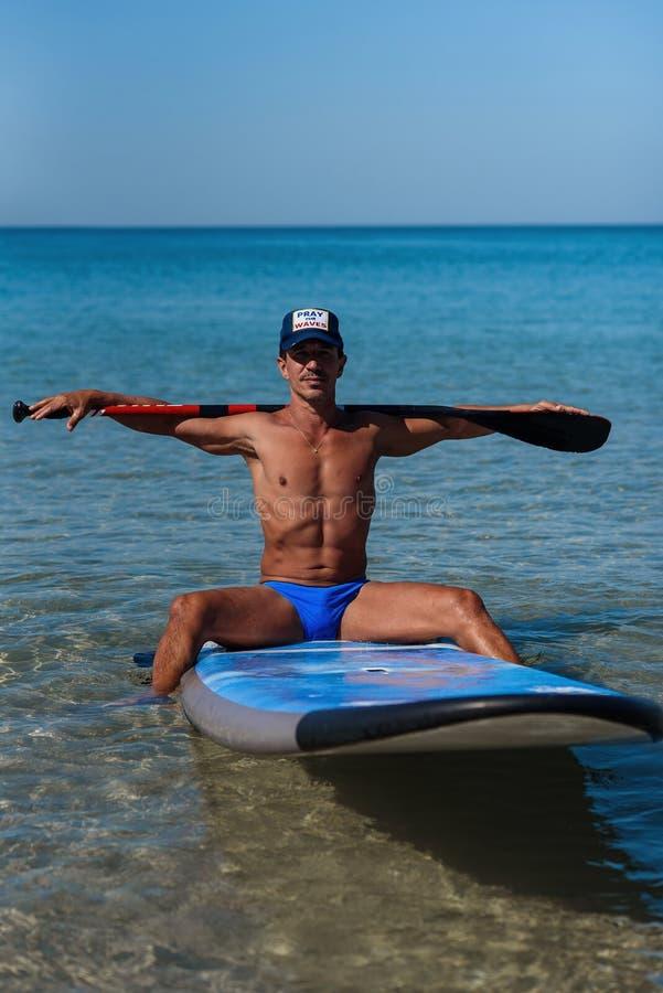 Загоренный sporty человек в крышке сидит на его surfboard на воде держа руками весло за его головой и взглядами в стоковое фото