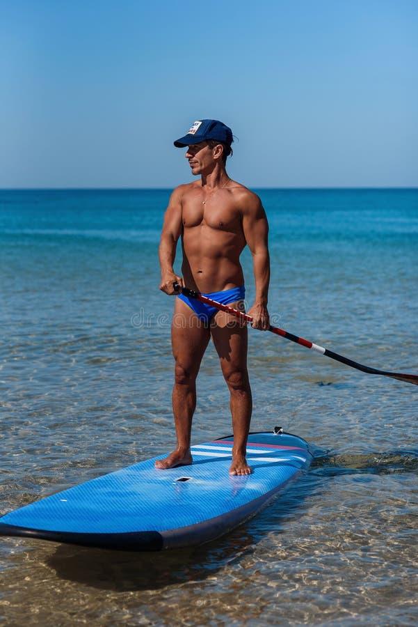 Загоренный sporty человек в крышке стоит на его surfboard на воде держа в руках весло и взгляды в море _ стоковая фотография rf