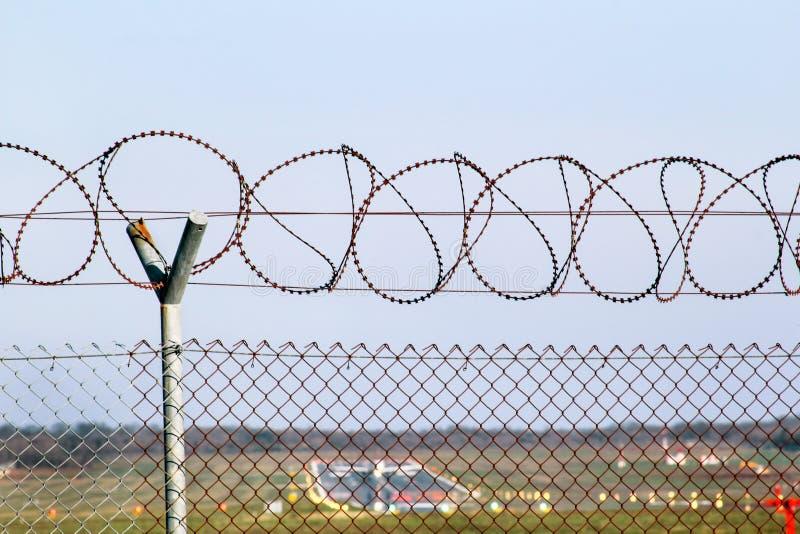 Загородка защитного провода колючая на авиапорте стоковое фото