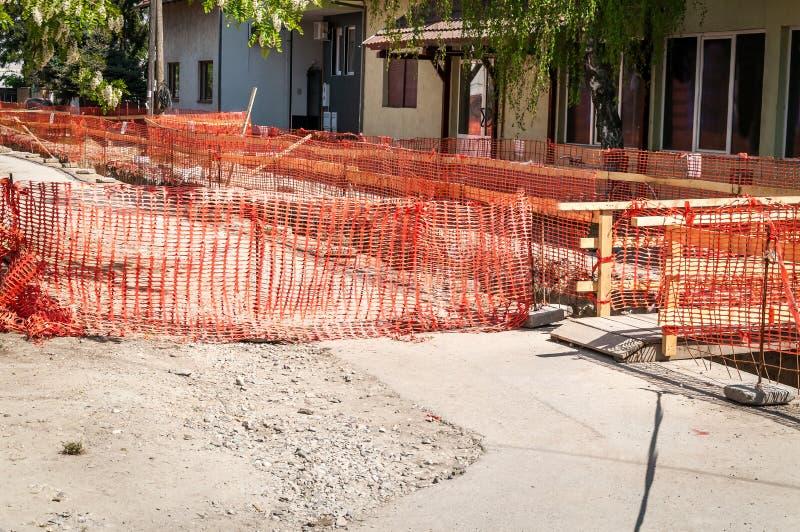 Загородка сети безопасности строительной площадки оранжевая как барьер над канавой на раскопк улицы для нового re трубопровода то стоковые изображения rf