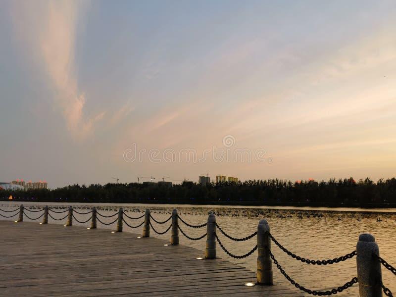 Загородка сформированная строкой каменных штендеров, заходящим солнцем, красивым составом озера стоковое изображение rf