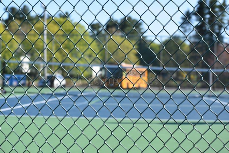 Загородка с теннисными кортами и школьным автобусом стоковое изображение