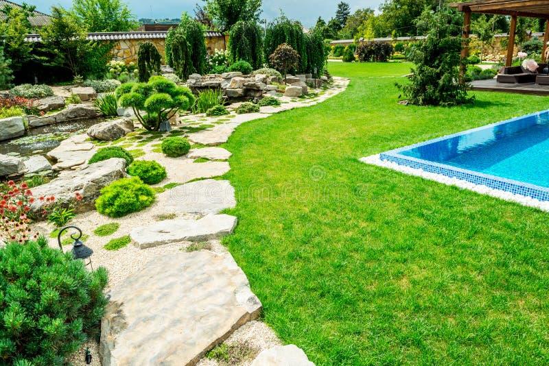 Загородный дом с красивой задворк за домом, дизайном ландшафта стоковая фотография