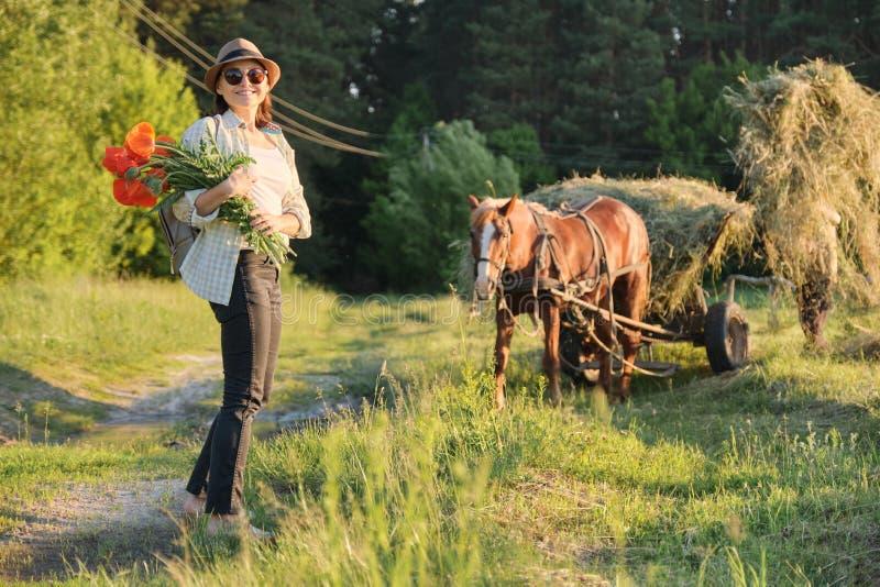 Загородный стиль, зрелая счастливая женщина в шляпе с букетами цветков маков идя вдоль проселочной дороги стоковое фото rf
