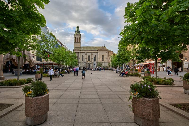 Загреб, Хорватия, 24-ое апреля 2019: Цветки придают квадратную форму, люди кофе идя, выпивать и предписывая весной после полудня стоковая фотография