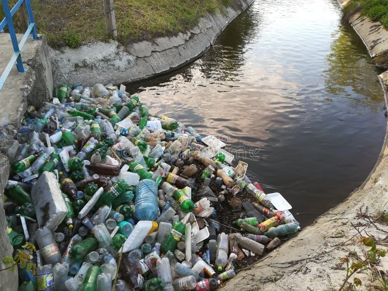 Загрязнение воды, пластиковые бутылки и отброс на поверхности реки стоковое изображение