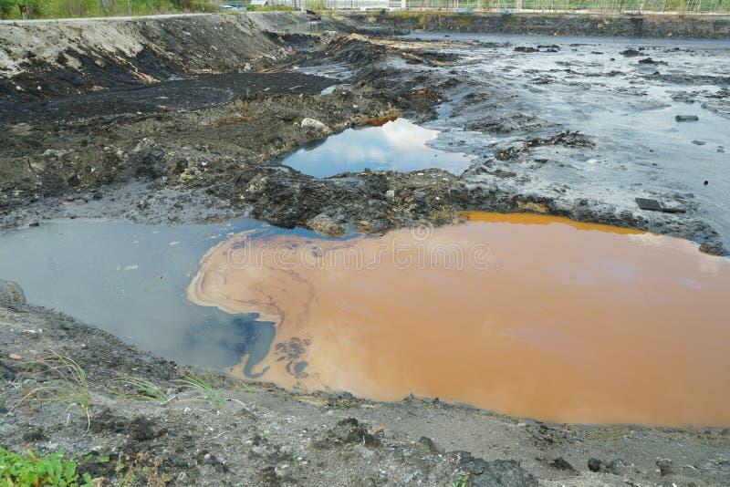 Загрязнения нефтью пятна почвы и воды загрязнения, бывшие ядовитые отходы сброса, природа влияний от загрязненной почвы и стоковые изображения rf