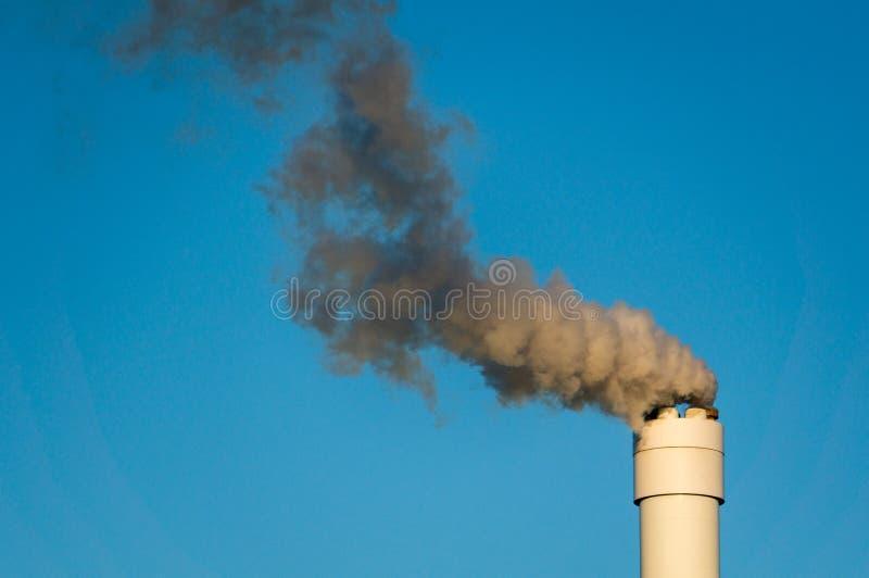 Загрязнянный дым против ясного голубого неба от высокорослой печной трубы стоковая фотография