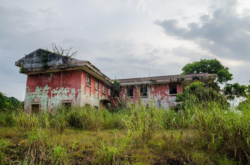 Загубленный особняк окруженный сочным зеленым цветом с драматическим небом Трассировки гражданской войны в Robertsport, Либерии стоковая фотография rf