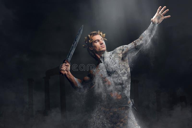 Задавливать каменный человеческий спортсмена держит шпагу стоковая фотография rf