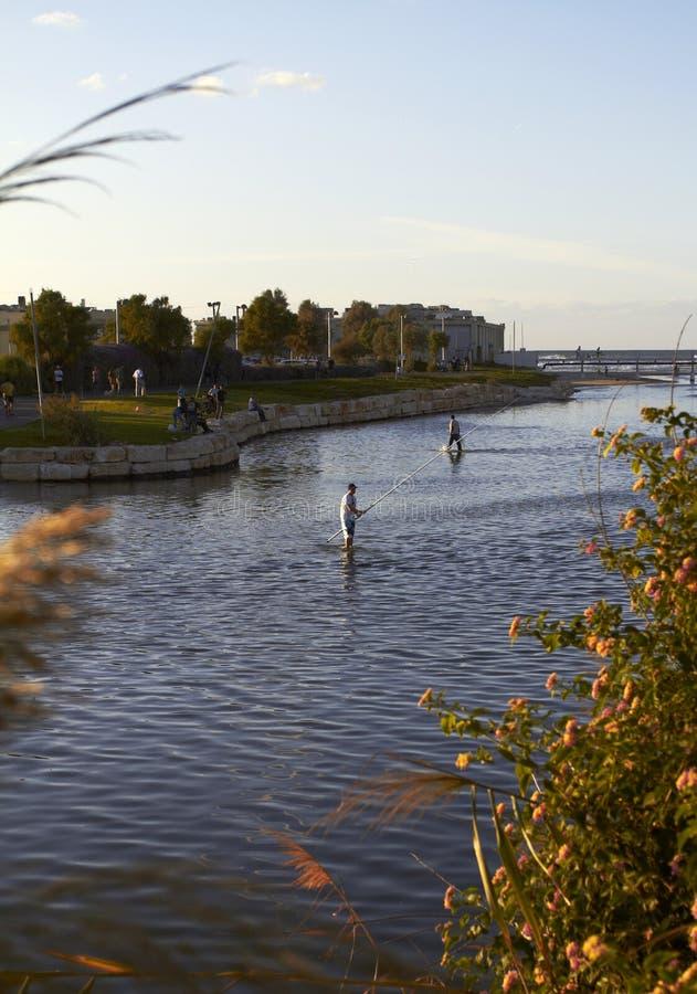 Задвижки рыболова удят в реке на заходе солнца против сини стоковые изображения rf
