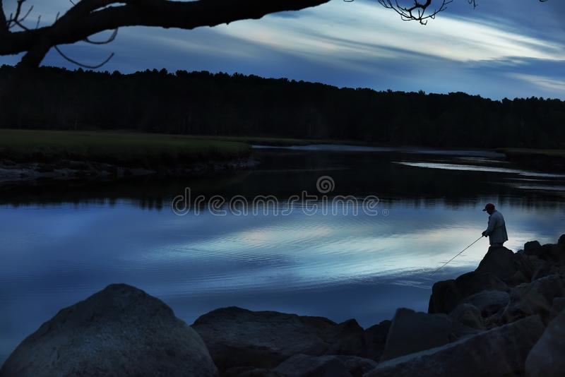 Задвижки рыболова удят на сумраке на перерыве реки на фото леса темном хмуром r Мейн удить в США стоковая фотография