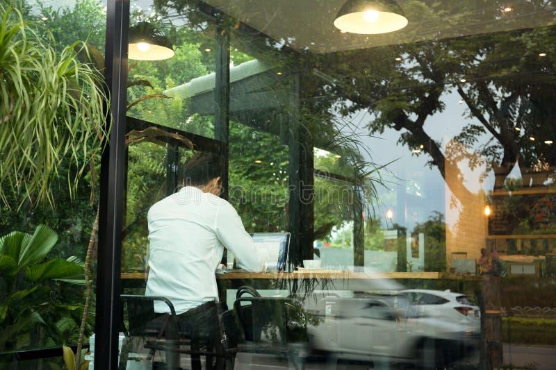 Задний бизнесмен взгляда сидя в кофейне используя compu компьтер-книжки стоковое изображение rf