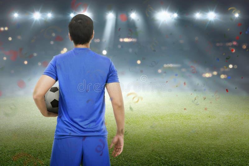 Задний взгляд азиатского футболиста стоя с шариком стоковое изображение rf