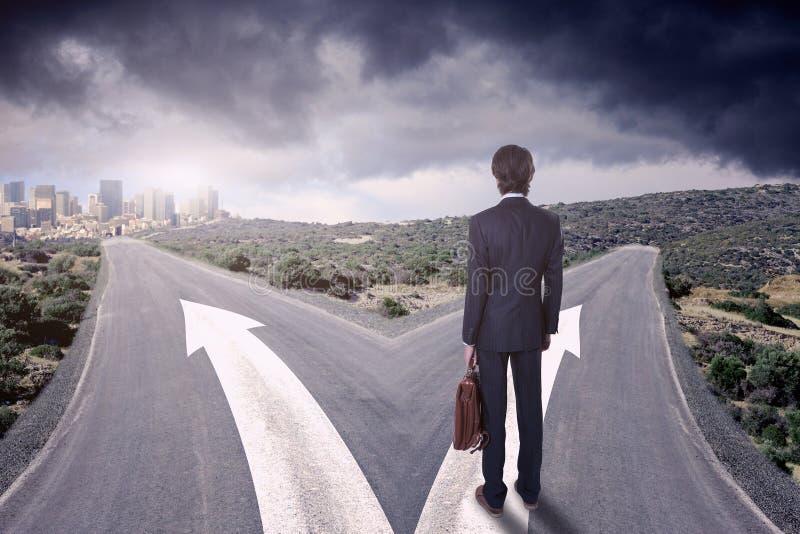 Задний взгляд бизнесмена стоя на перекрестках стоковая фотография