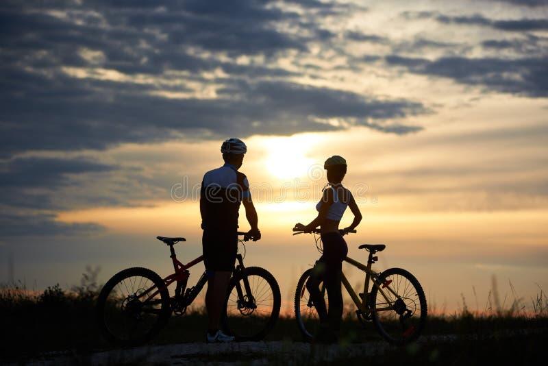 Задний взгляд велосипедистов пар стоя с велосипедами и наслаждаясь заходом солнца стоковое фото rf