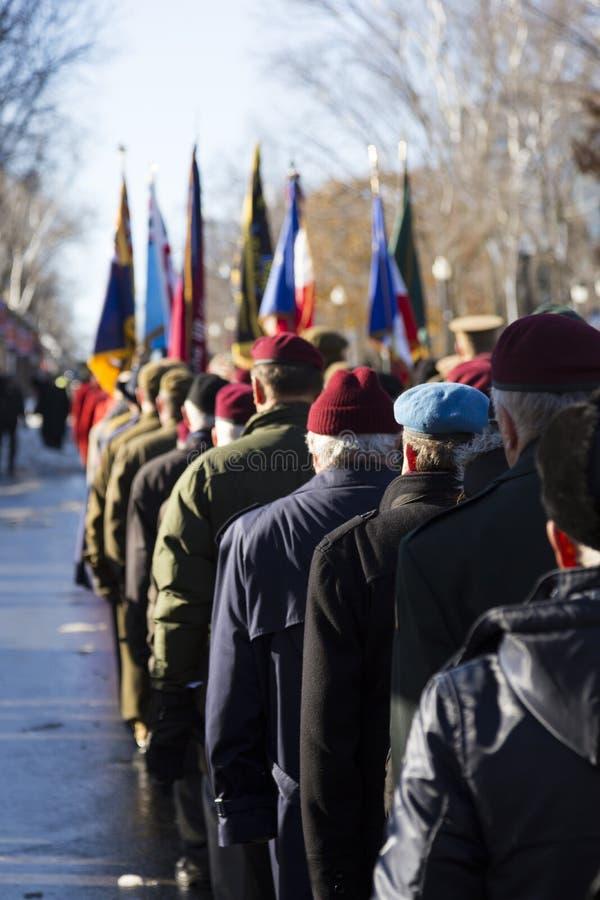 Задний взгляд ветеранов от различных полков и групп проходя парадом на церемонии дня памяти погибших в первую и вторую мировые во стоковые фото