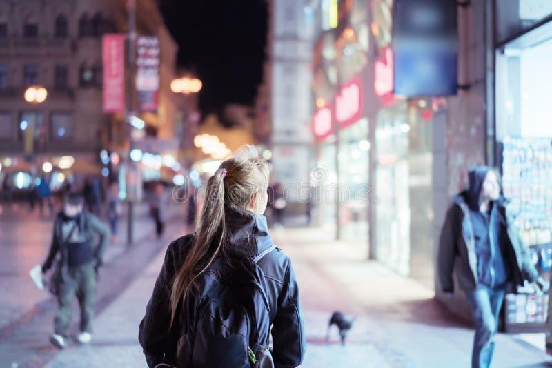 Задний взгляд девушки идя на улицу города на ноче стоковое фото rf