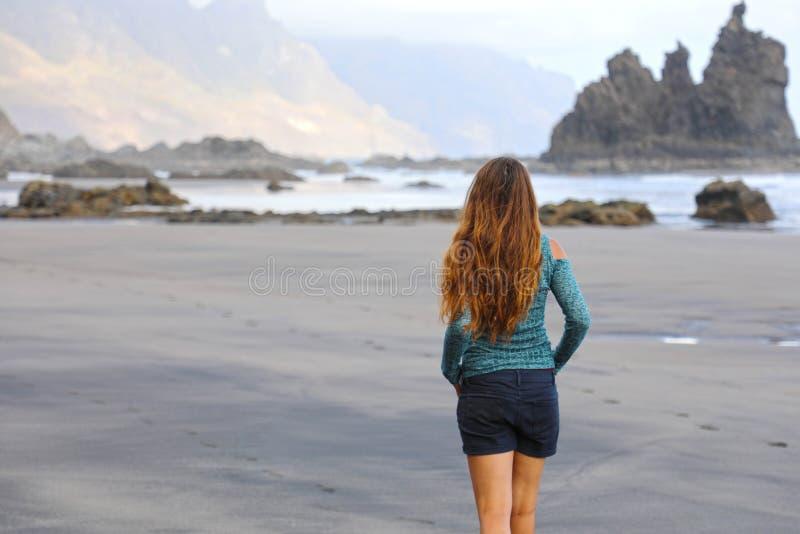 Задний взгляд девушки идя рефлексивный e спокойный на спрятанном изумительном черном пляже на восходе солнца Молодое женское откр стоковое фото rf