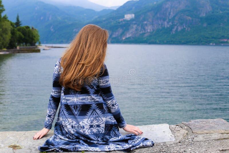 Задний взгляд девушки сидя около озера Como, горы в предпосылке стоковые изображения