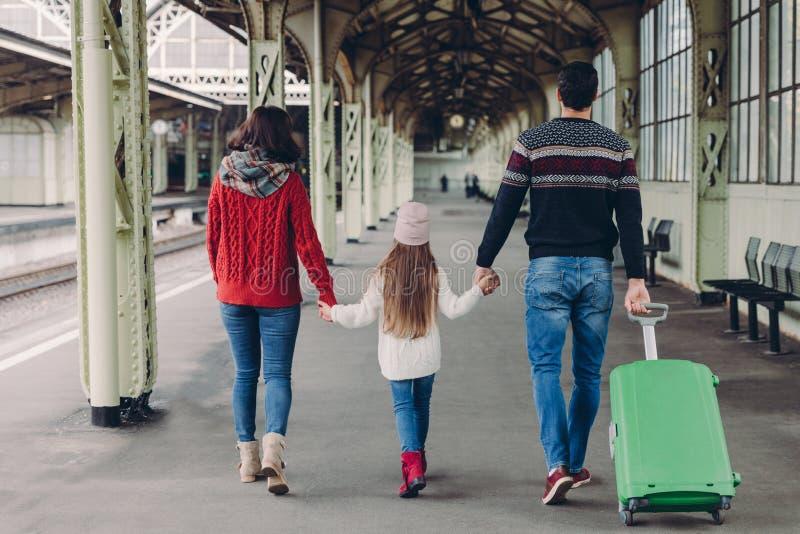 Задний взгляд дружелюбных рук владением семьи, носит чемодан, идя иметь отключение рейса, представляет на платформе железнодорожн стоковые фото