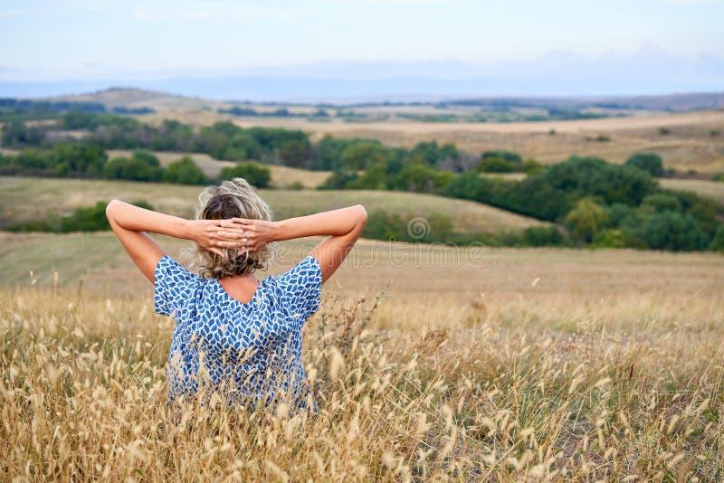Задний взгляд женщины сидя в сухой неурожайной траве, смотря в горизонте стоковые изображения