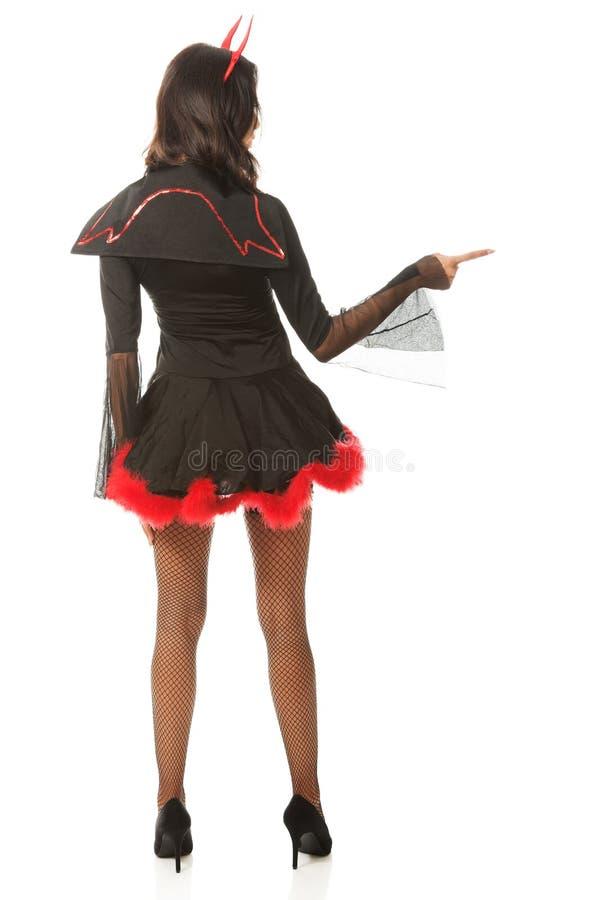 Задний взгляд женщины указывая справедливо нося дьявол одевает стоковая фотография